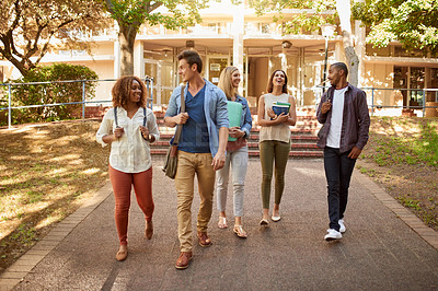 Buy stock photo Full length shot of a group of college students enjoying walking together between classes on campus
