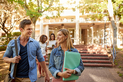 Buy stock photo Cropped shot of a young couple walking together between classes with their classmates in the background