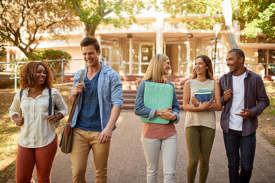 Buy stock photo Cropped shot of a group of college students enjoying walking together between classes on campus