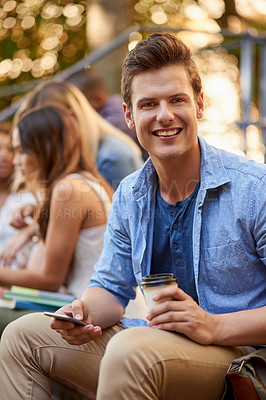 Buy stock photo Cropped portrait of a handsome young male student siting outdoors on campus with his classmates in the background