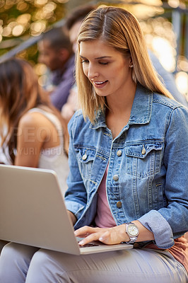 Buy stock photo Cropped shot of an attractive young female student using her laptop while sitting outdoors on campus