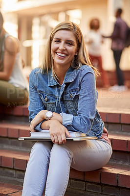 Buy stock photo Cropped portrait of an attractive young female student sitting with books on her laps outdoors on campus