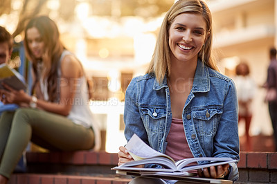 Buy stock photo Cropped portrait of an attractive young female student using a textbook to study while sitting outdoors on campus