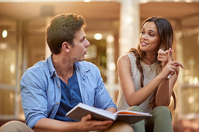 Buy stock photo Cropped shot of a young couple studying together outdoors on campus