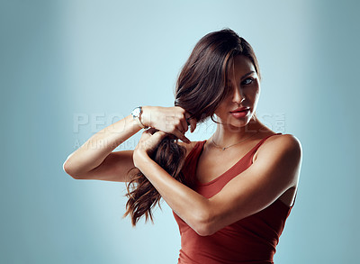 Buy stock photo Studio shot of an attractive young woman pulling her hair against a blue background