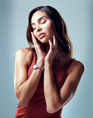 Buy stock photo Studio shot of an attractive young woman holding her face against a blue background