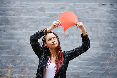 Buy stock photo Cropped shot of an attractive young woman looking skeptical while holding up a speech bubble against a grey wall