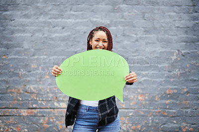 Buy stock photo Cropped portrait of an attractive young woman holding a speech bubble while standing against a grey wall