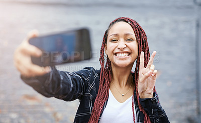 Buy stock photo Cropped portrait of an attractive young woman taking a selfie while making a peace sign against a grey wall