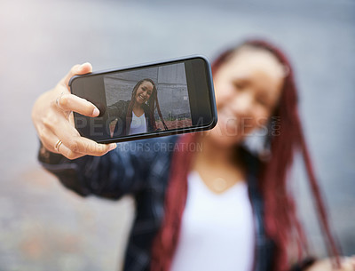 Buy stock photo Cropped shot of a young woman taking a selfie with her smartphone while standing against a grey wall