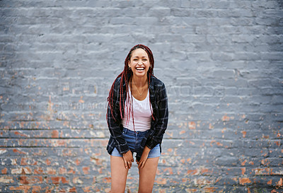 Buy stock photo Cropped portrait of an attractive young woman laughing while standing against a grey wall
