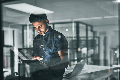 Buy stock photo Cropped shot of a handsome young businessman working late in the office