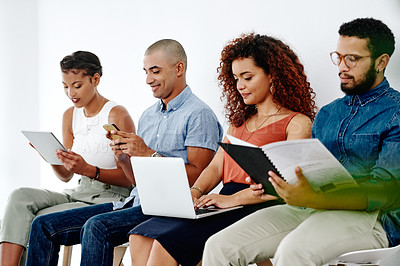 Buy stock photo Shot of young businesspeople sitting down and preparing for their interviews against a white background