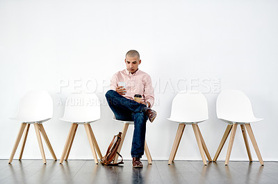 Buy stock photo Shot of a young businessman sitting down and preparing for an interview against a white background