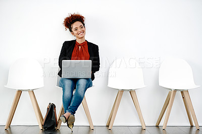 Buy stock photo Full length shot of an attractive young businesswoman using a laptop while sitting down and preparing for her interview