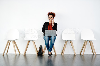 Buy stock photo Portrait of an attractive young businesswoman using a laptop and taking a phone call while waiting for her interview