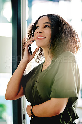 Buy stock photo Shot of a young businesswoman talking on her cellphone at the office