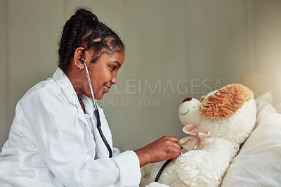 Buy stock photo Shot of a young girl pretending to be a doctor while while playing with her teddybear