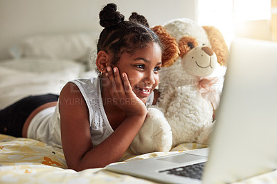 Buy stock photo Shot of a young girl lying on bed with her teddybear while watching something on her laptop