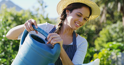 Buy stock photo Cropped shot of an attractive young female farmer watering her crops on the farm