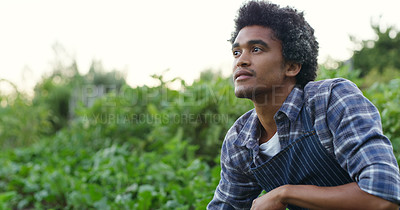 Buy stock photo Cropped shot of a handsome young male farmer looking thoughtful while checking on his crops on the farm