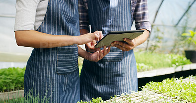 Buy stock photo Cropped shot of an unrecognizable couple using a tablet while working in a greenhouse on their farm