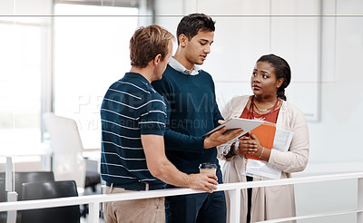 Buy stock photo Shot of a diverse group of colleagues at work discussing ideas on a tablet in the office