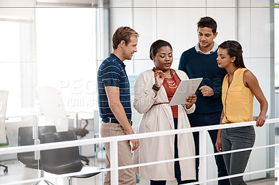 Buy stock photo Cropped shot of a diverse group of business people at work discussing ideas on a tablet in the office