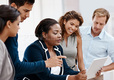 Buy stock photo Cropped shot of a diverse group of colleagues at work discussing ideas on a tablet in the office