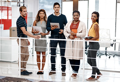 Buy stock photo Full length shot of a diverse group of colleagues standing together in the office and smiling at the camera