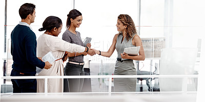 Buy stock photo Shot of a young diverse group of colleagues shaking hands in agreement at the office