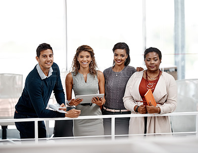 Buy stock photo Shot of a diverse young group of colleagues standing together in the office and smiling at the camera