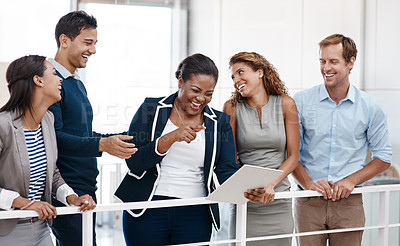 Buy stock photo Shot of a happy group of colleagues sharing a laugh together in the office