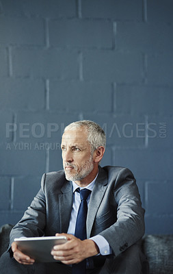 Buy stock photo Cropped shot of a handsome and thoughtful mature businessman using a digital tablet in his office