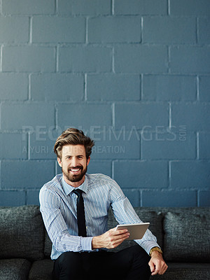 Buy stock photo Cropped portrait of a handsome young businessman using his digital tablet in the office