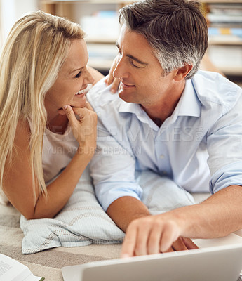 Buy stock photo Cropped shot of an affectionate mature couple lying on their living room floor doing some online research