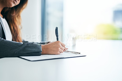 Buy stock photo Cropped shot of an unrecognizable businesswoman going over paperwork at her desk in a modern office