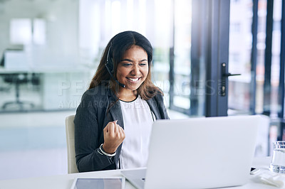 Buy stock photo Shot of a young woman cheering while using a headset and laptop in a modern office