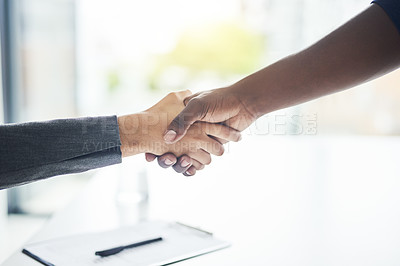 Buy stock photo Cropped shot of an unrecognizable businessman and businesswoman shaking hands in a modern office