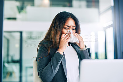 Buy stock photo Shot of a young businesswoman blowing her nose with a tissue in a modern office