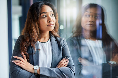 Buy stock photo Shot of a young businesswoman looking thoughtful while working in a modern office