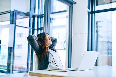 Buy stock photo Shot of a young businesswoman taking a break at her desk in a modern office