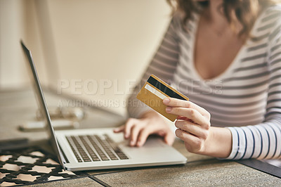 Buy stock photo Cropped shot of an unrecognizable young woman's hand holding a credit card while shopping online