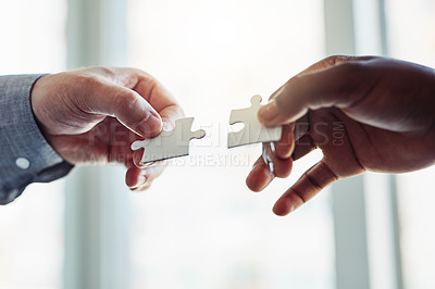 Buy stock photo Cropped shot of two businessmen joining two puzzle pieces together in a modern office