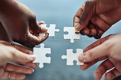 Buy stock photo Cropped shot of a group of businesspeople joining puzzle pieces together in a modern office