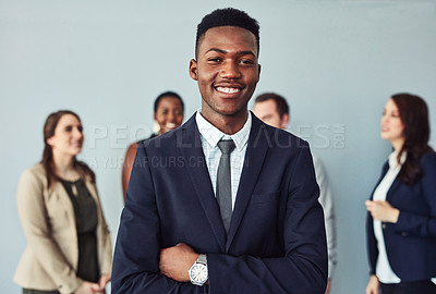Buy stock photo Studio portrait of a confident young businessman standing in front of his colleagues against a grey background