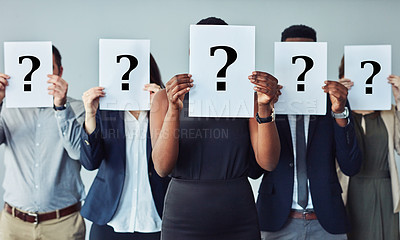 Buy stock photo Studio shot of a group of businesspeople holding questions marks in front of their faces