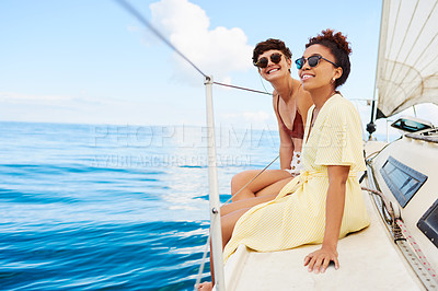 Buy stock photo Shot of two happy young women enjoying a relaxing day on a yacht