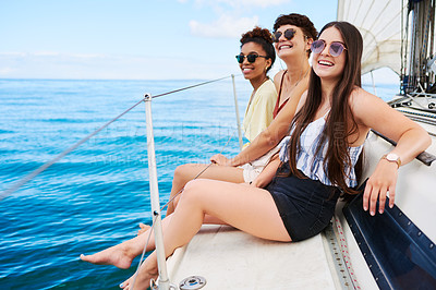 Buy stock photo Shot of a group of happy young women enjoying a relaxing day on a yacht
