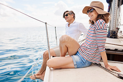 Buy stock photo Shot of an affectionate couple enjoying a boat cruise out on the ocean
